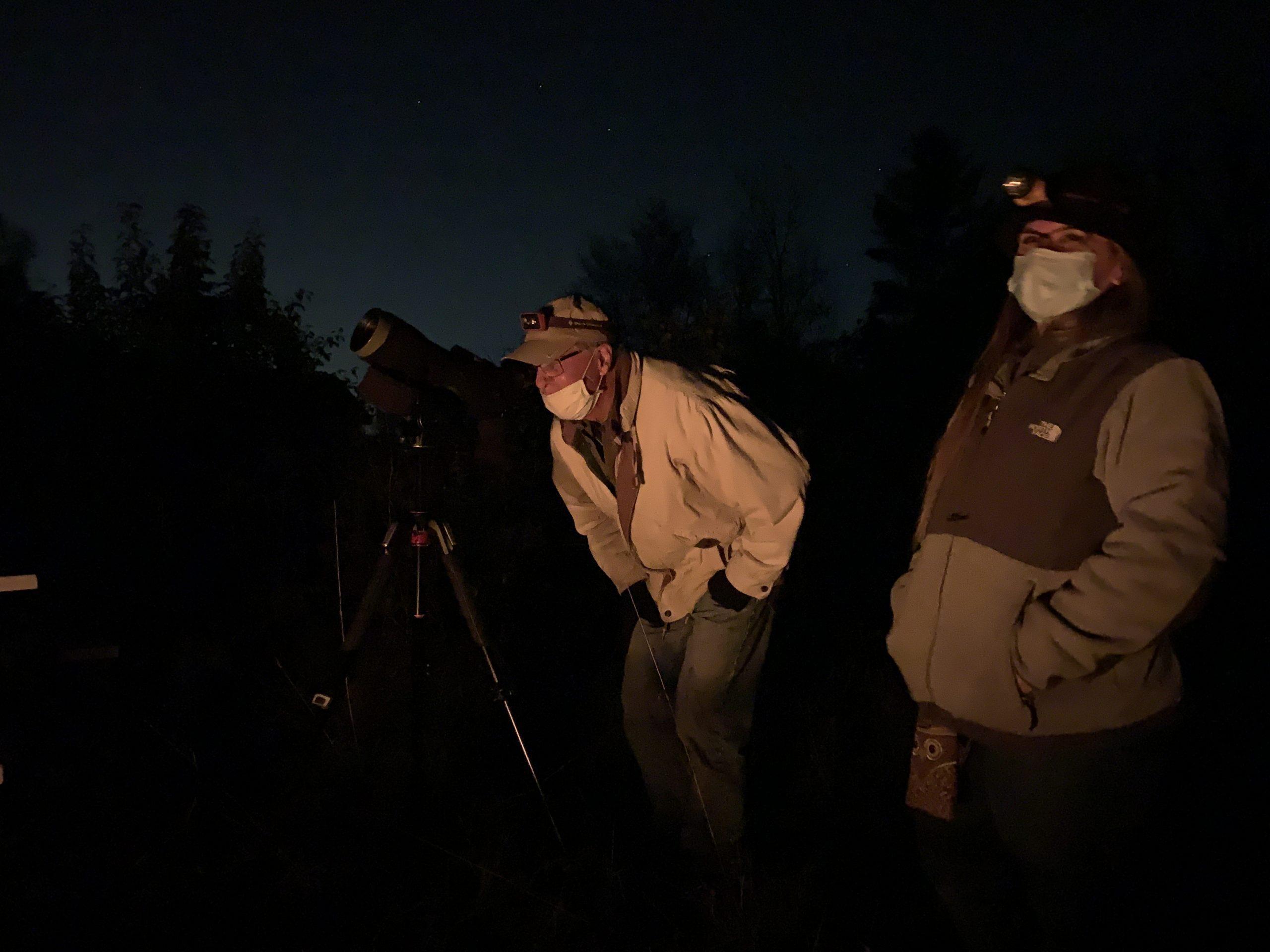 Stargazers look through a telescope at night